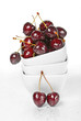 Fresh cherry berries in a stack of white ceramic bowls