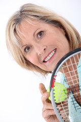 Blond woman holding tennis racket and ball