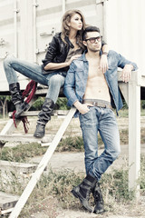 stylish couple wearing jeans and boots posing dramatic