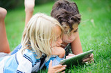 two children lying on the grass looking at something on the tabl