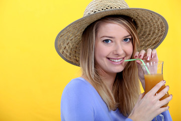 Woman in straw hat drinking tropical drink