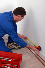 Plumber measuring a wall