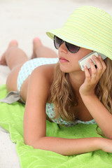 Woman laying on the beach with mobile telephone