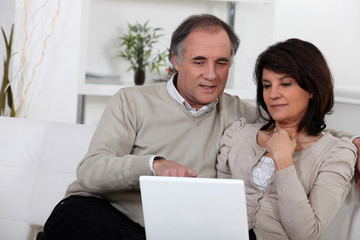 Mature couple on a sofa with laptop computer