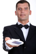 Male waiter holding credit-card and receipt
