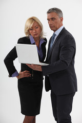 businessman and businesswoman looking at a laptop