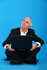Senior businessman sat on the floor with laptop