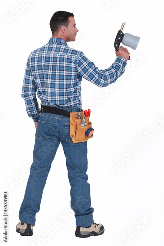 A male construction worker holding a welding torch.