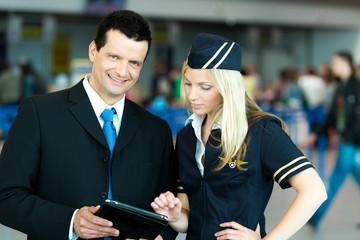Stewardess und Business-Mann betrachten etwas am Tablett