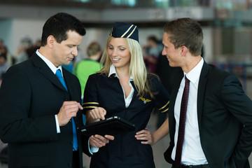 Stewardess zeigt Business-Männern etwas auf dem Tablet