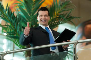 Business-Mann mit Daumen hoch und Tablet