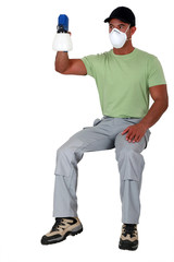 Man sitting on an invisible stool and holding a spray gun
