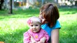 Happy Mother and her baby girl enjoy playing outdoor