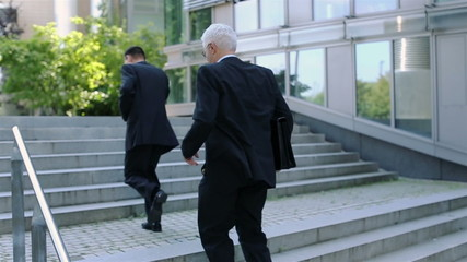 Businessmen running stairs in slow motion
