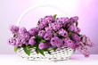 beautiful lilac flowers in basket on purple background