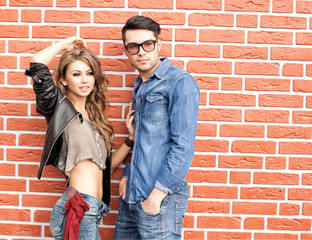 attractive fashionable couple casually leaning against wall