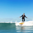 Businessman surfing on the waves of the ocean