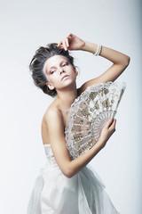 Enigma. Fantasy. Retro fashion woman with white vintage fan