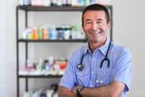 Mature Doctor Standing In Front Of Medicine