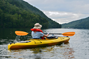 Woman Kayaking on Mountain Lake