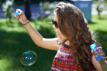 Young girl blows soap bubbles