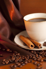 Cup of coffee with cinnamon and beans