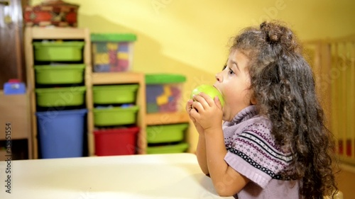 Children and healthy food, baby girl eating fruit at school