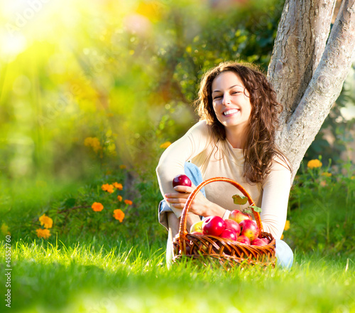 Beautiful Girl Eating Organic Apple in the Orchard