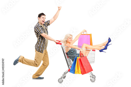Excited person pushing a smiling woman with bags in a shopping c