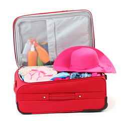 Suitcase with summer clothes, a hat and suntan isolated on