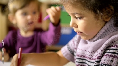 Children and fun, two happy preschoolers drawing in kindergarten
