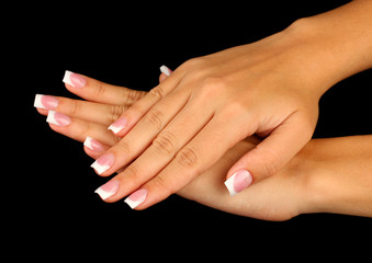 Beautiful woman's hands with french manicure on black