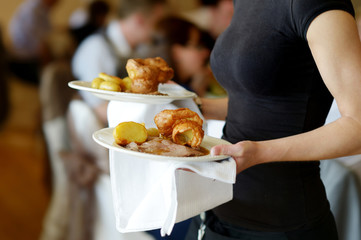 Waitress carrying two plates with meat dish