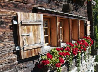 Typisches Fenster mit Blumen in den schweizer Bergen