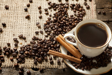 Cup of coffee with beans and cinnamon vintage background