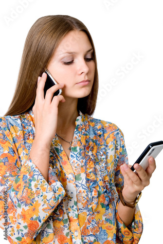 Young business woman with two mobile phones in talks.