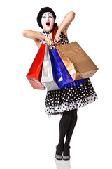 Funny mime in spotty dress holding shopping bags