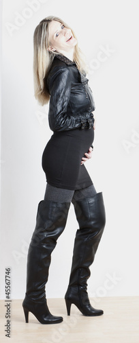 standing pregnant woman wearing fashionable black boots