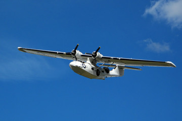 Seaplane Catalina in flight on blue sky