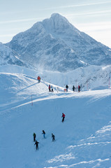 People on the snow-covered mountain peaks and rocky peaks.