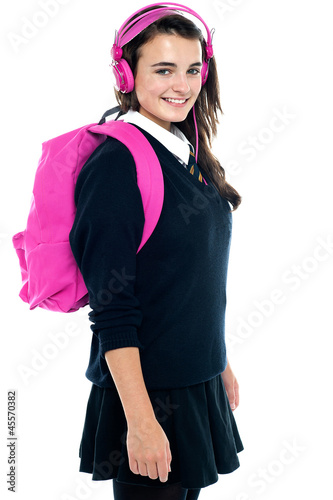 Schoolgirl with pink backpack and matching headphones