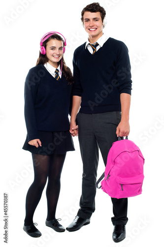 Boy holding pink backpack posing with female student