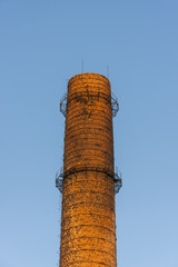 Red brick chimney on blue sky background