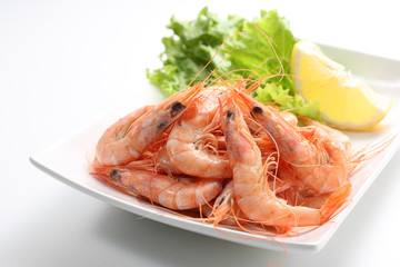 dish of fresh boiled prawns with lettuce, isolated on grey