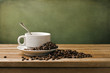 White cup and coffee beans on wooden table and grunge background
