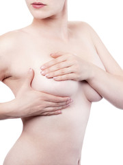Young woman examining her breasts - isolated
