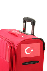 red suitcase with sticker with flag of Turkey isolated on white