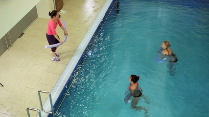 Instructor training women aqua gymnastic in swimming pool