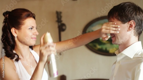 Bride nebulizes varnish on a groom