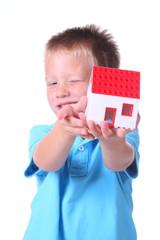 Kind mit seinem Haus